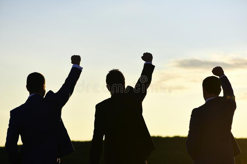 Silhouettes of men putting their fists up. Victory and success stock image