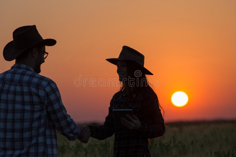 Farmers shaking hands at sunset stock images