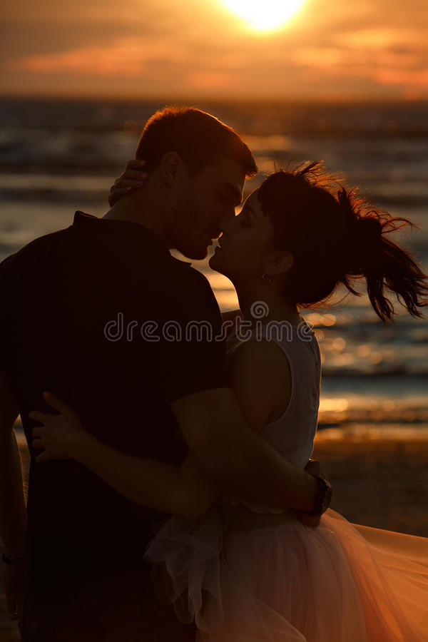Silhouettes of men and women in the lush short skirt, kissing ag royalty free stock image