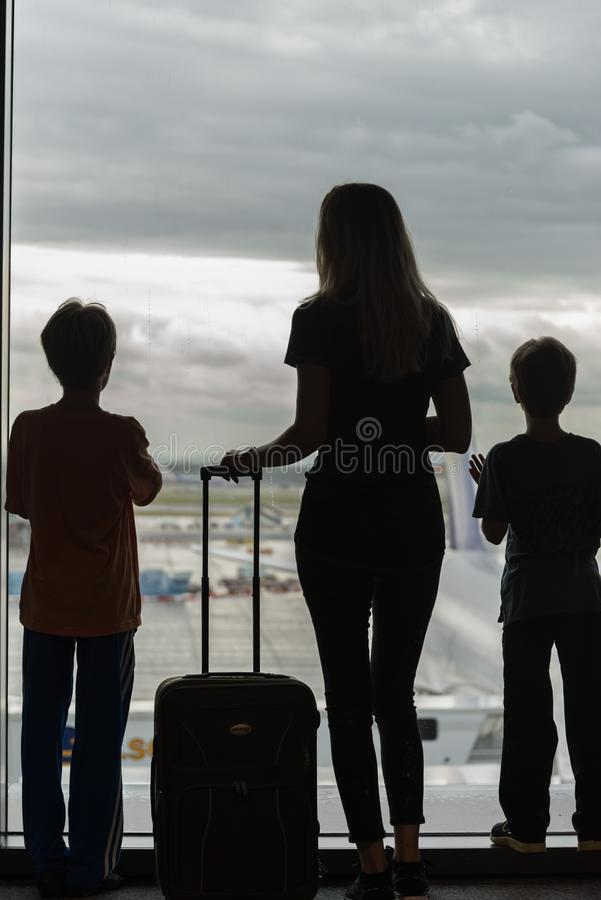 Silhouettes of mom with kids in terminal waiting for flight stock photos
