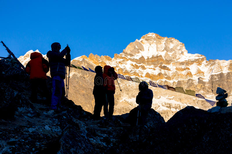 Silhouettes of Mountain Climbers against high Peaks. Silhouettes of Mountain Climbers talking and taking Pictures on rocky place in front of high Summit royalty free stock photo