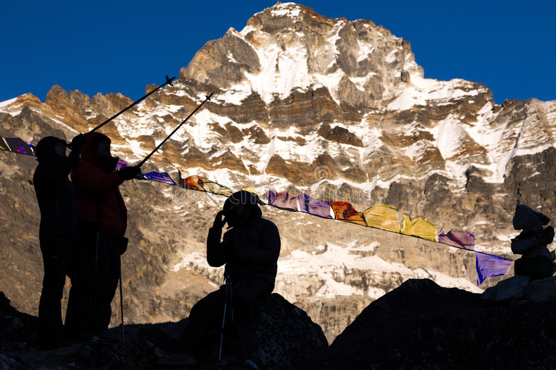 Silhouettes of Mountain Climbers pointing to high Peaks stock image