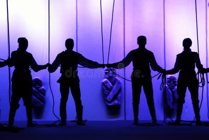 Silhouettes noires des personnes tenant des mains sur l'étape du théâtre devant les cordes photo stock