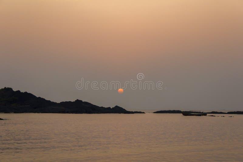 Silhouettes noires des roches et le soleil au-dessus de l'océan le soir, vue de la mer image stock