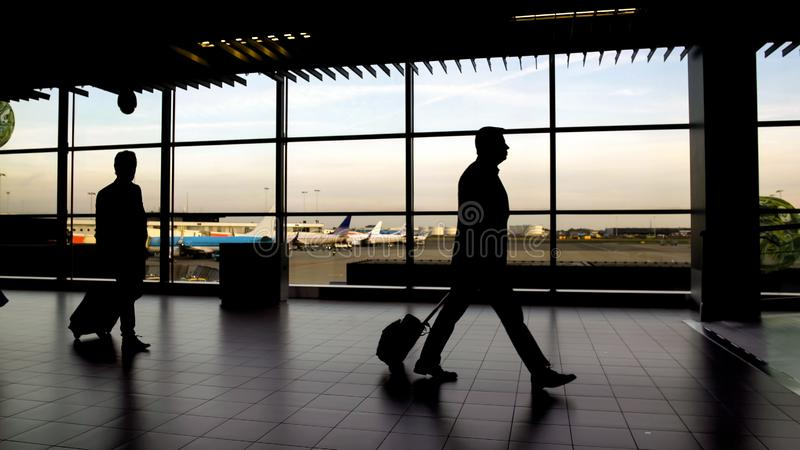 Silhouettes of passengers walking at terminal hall, business trip, airport royalty free stock image
