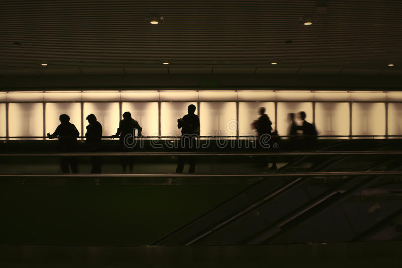 Silhouettes of people backlit in a dark subway station. stock image