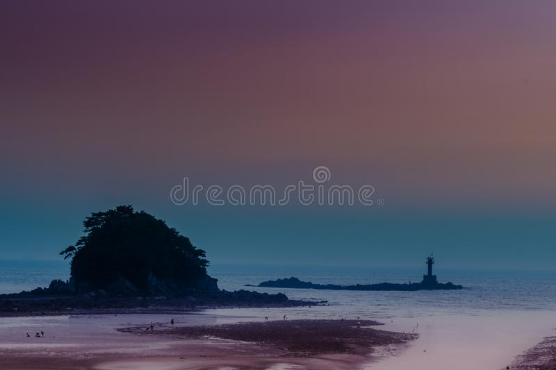 Silhouettes of people on beach. In front of ocean islet at low tide with beautiful sky in background royalty free stock photo