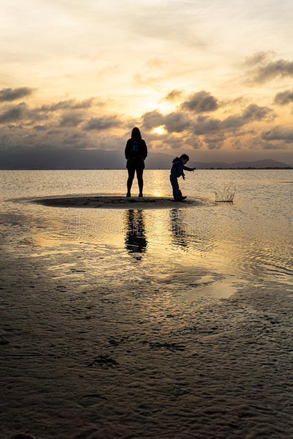 Silhouettes of unrecognizable people on the beach at sunset stock photography