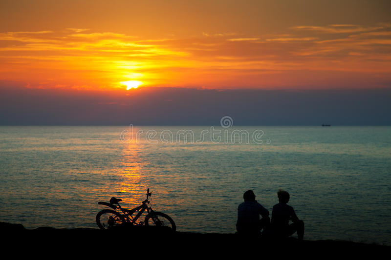 Silhouettes of people on the beach. At sunset stock photography