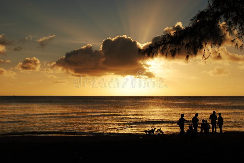 Silhouettes of people on the beach at sunset. Gorgeous clouds and silhouettes of people on the beach at sunset royalty free stock image