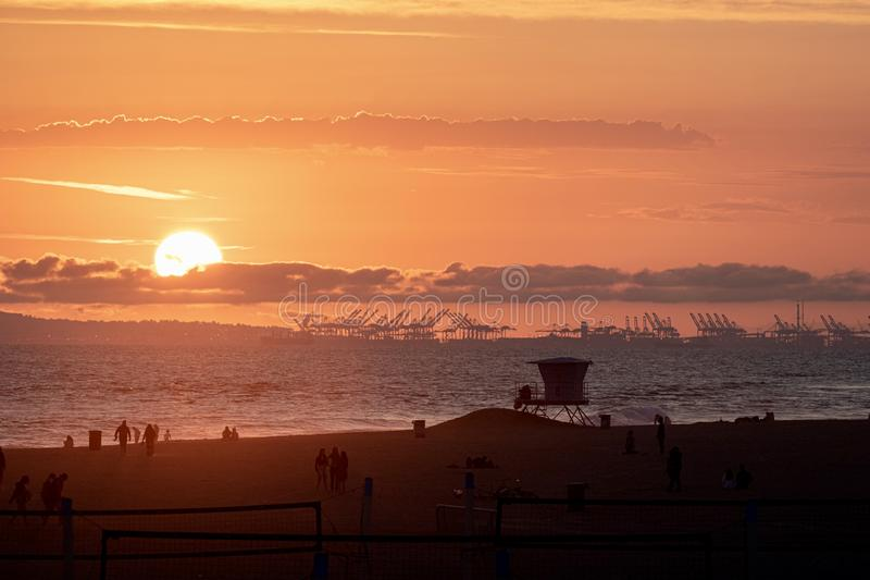 Silhouettes of people on the beach during sunset. Silhouettes of people on a beach during a bright orange sunset in Huntington Beach California showing the port stock image
