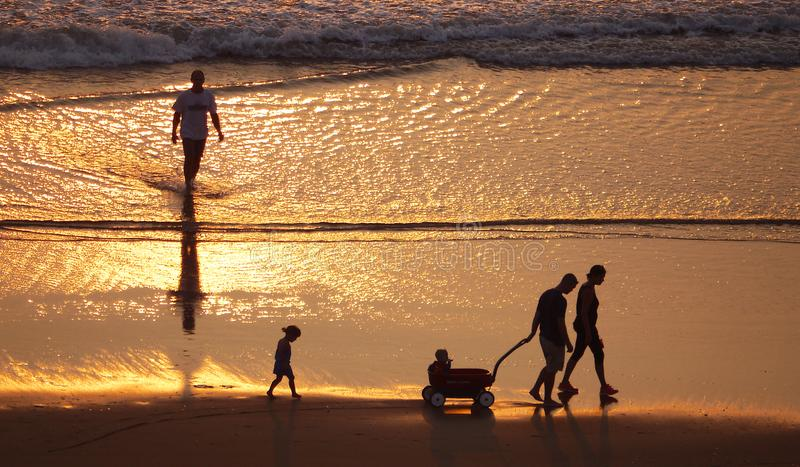 Silhouettes of people on the beach stock photography