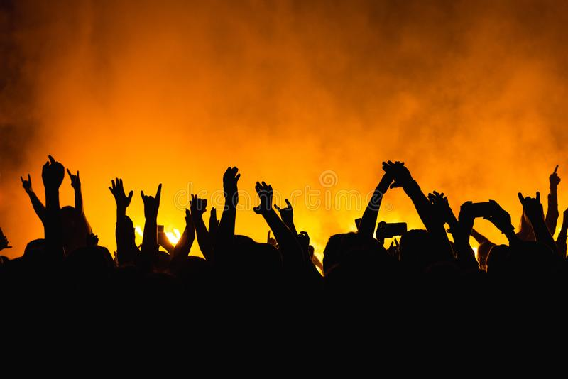 Silhouettes of concert crowd in front of bright stage lights. Dancing people with hands on against stage light. Fans burn yellow royalty free stock photography
