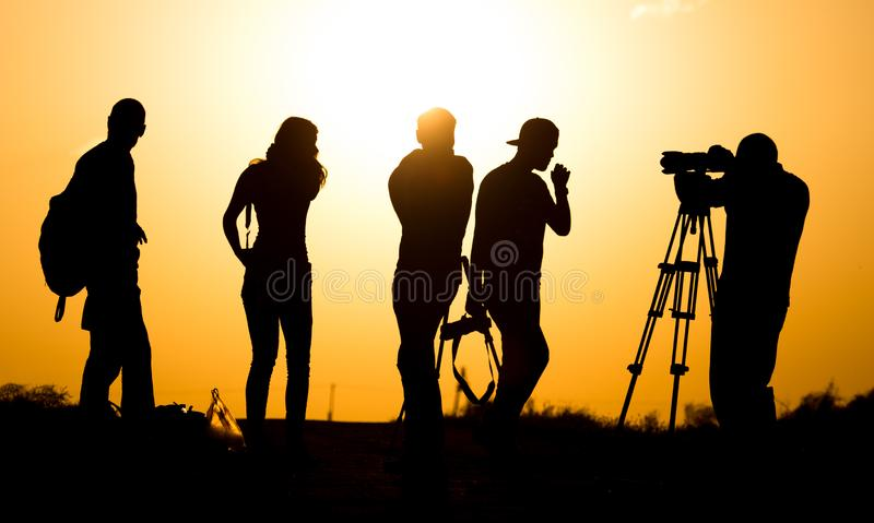 Silhouettes of people with cameras at sunset.  royalty free stock image