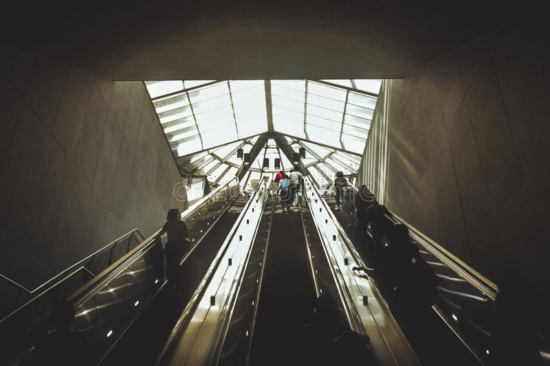 Silhouettes of people coming from the escalator.  royalty free stock image