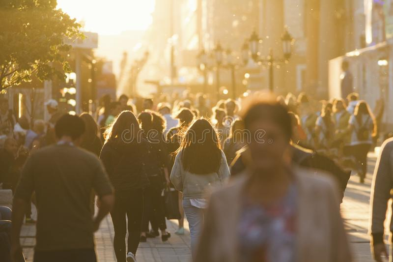 Silhouettes of people crowd walking down the street at summer evening, beautiful light at sunset stock image