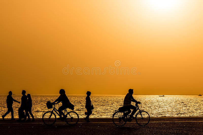 Silhouettes of people enjoying a walk by the seaside of the town royalty free stock photo