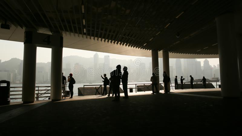 Silhouettes of people in the harbor of Victoria in Hong Kong. View of the sea and the city from inside the bridge stock images