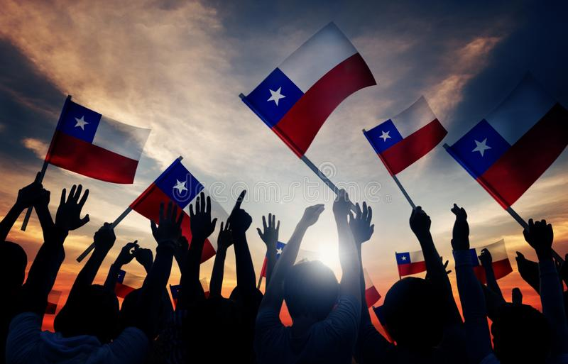 Silhouettes of People Holding Flag of Chile stock photo