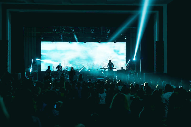 Silhouettes of people and musicians in big concert stage stock images