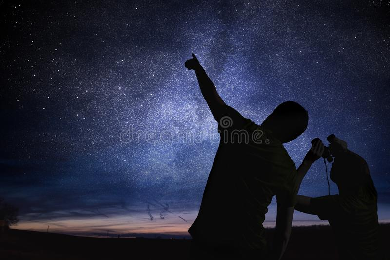 Silhouettes of people observing stars in night sky. Astronomy concept.  stock photos