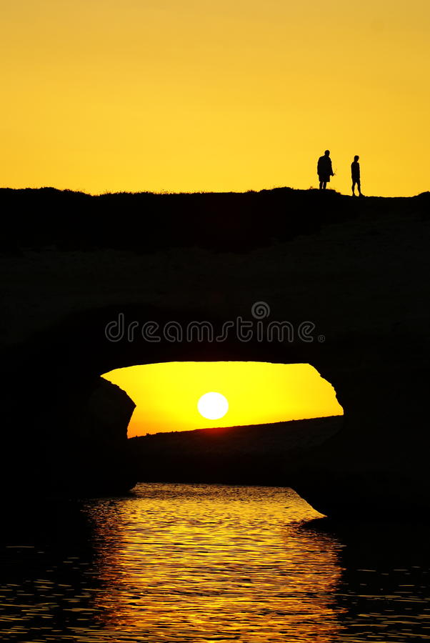 Silhouettes of people over the sea in the sunset royalty free stock image