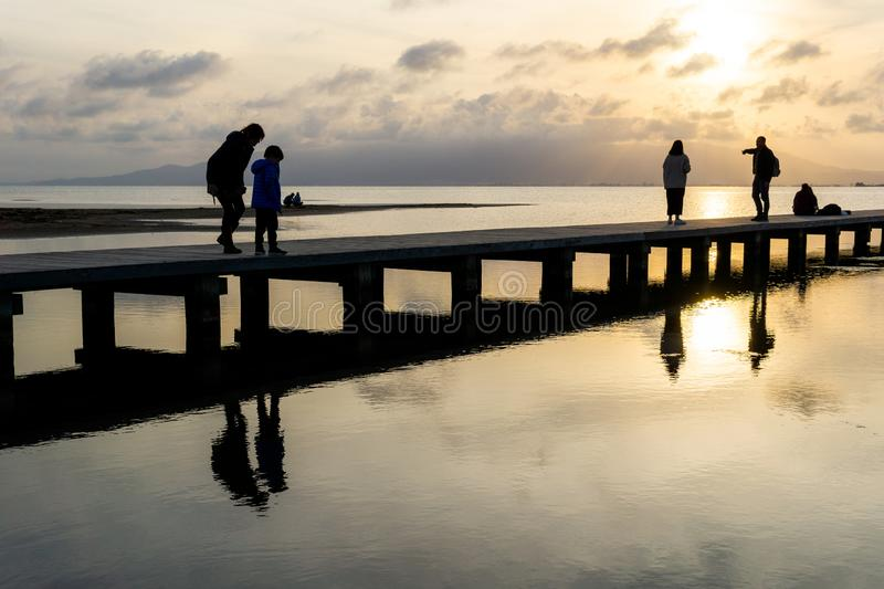 Silhouettes of unrecognizable people on a pier at sunset royalty free stock photos