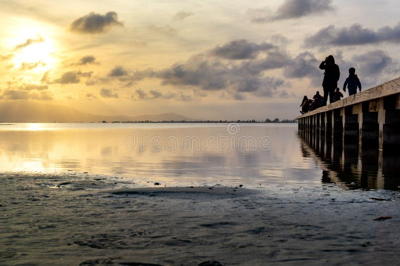 Silhouettes of unrecognizable people on a pier at sunset stock photography
