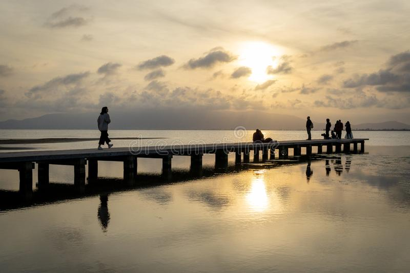 Silhouettes of unrecognizable people on a pier at sunset stock images