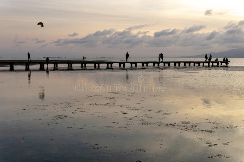 Silhouettes of unrecognizable people on a pier at sunset royalty free stock photo