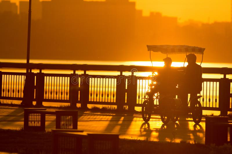 Silhouettes of people on the promenade riding on multi-seat bike at sunset stock photography
