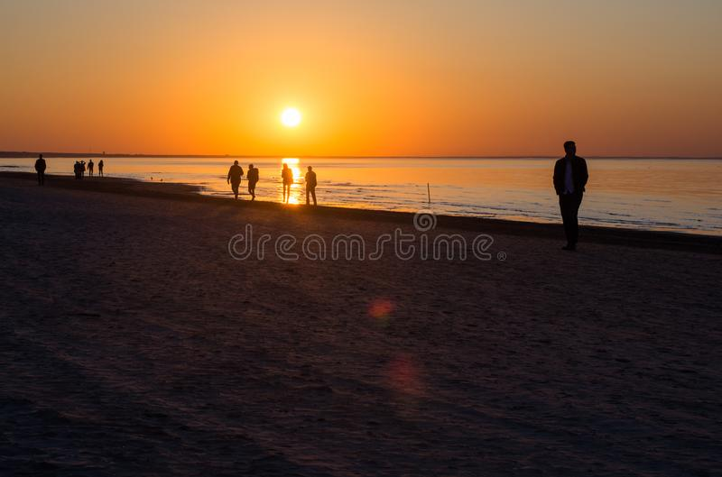 Silhouettes of people at sea during sunset. At summer royalty free stock photos
