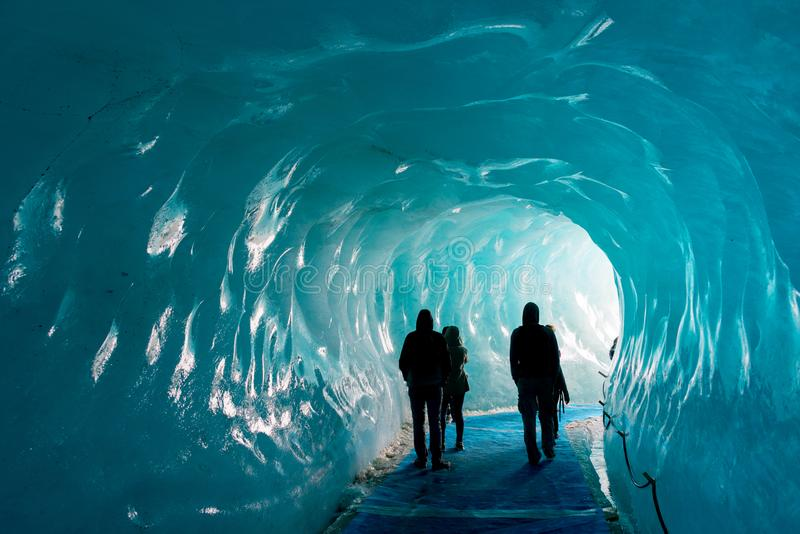 Silhouettes of people visiting thee ice cave of the Mer de Glace glacier, in Chamonix Mont Blanc Massif, The Alps France. Silhouettes of people visiting thee ice royalty free stock photography