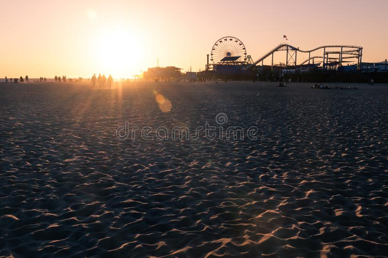 Silhouettes of people walking along Santa Monica beach and amusement park at sunset, Los Angeles, California royalty free stock photo