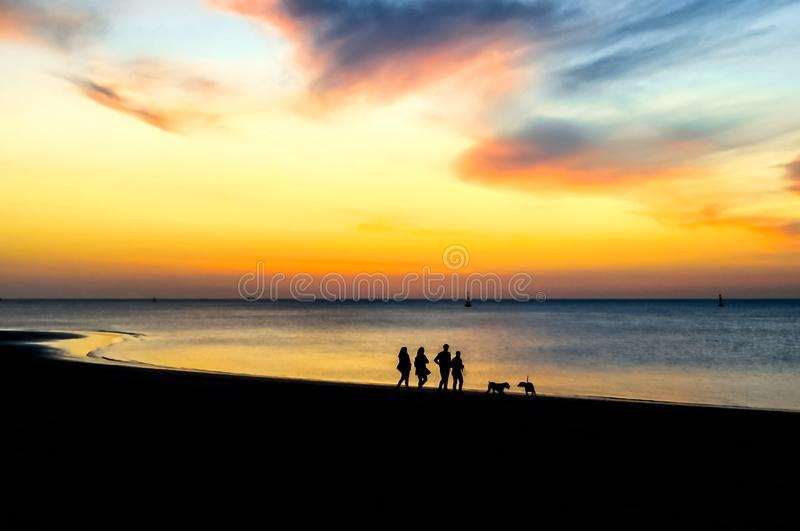 Silhouettes of people walking on the beach at sunset. Epic dramatic sunset. stock photos