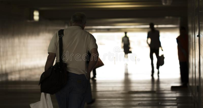 Silhouettes of people walking in a dark tunnel against a white glow royalty free stock images