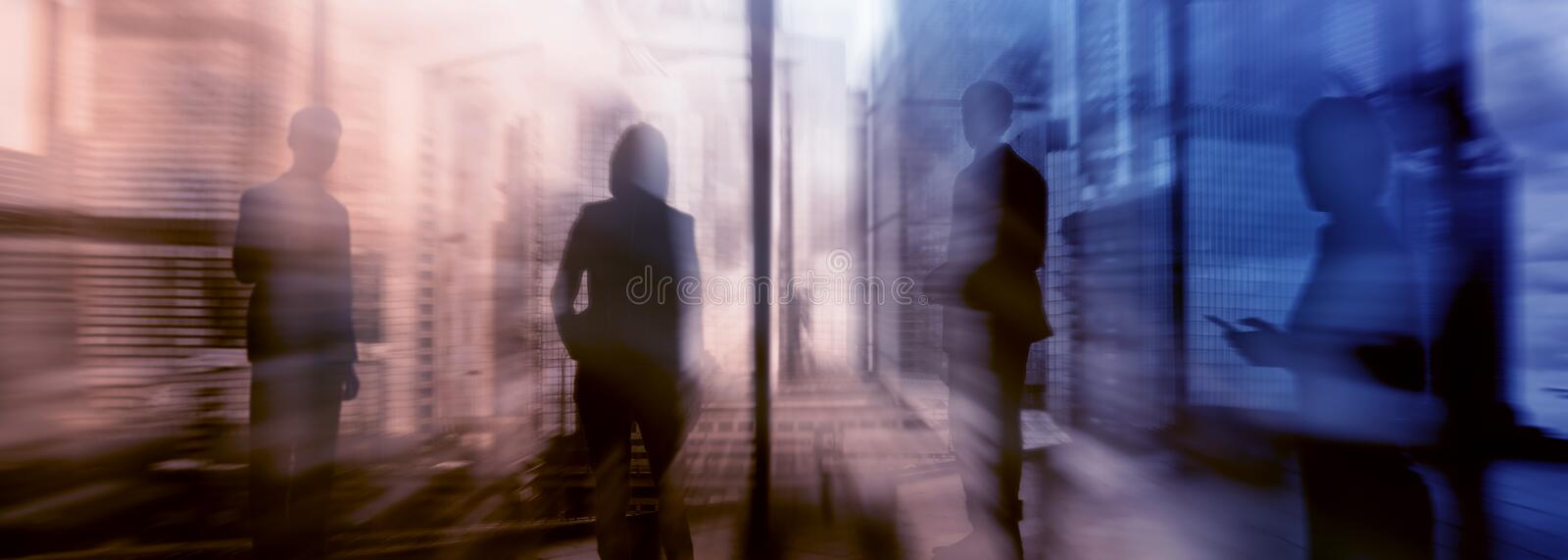 Silhouettes of people walking in the street near skyscrapers and modern office buildings. Multiple exposure blurred image. stock images