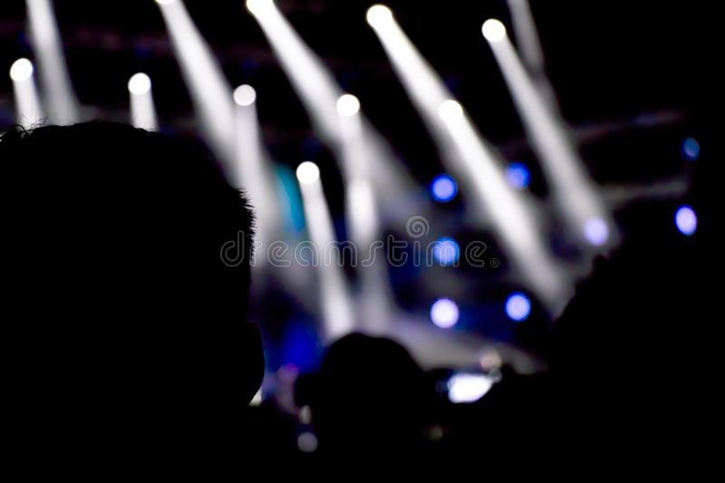 Silhouettes of people watching the concert and stage light. Silhouettes of people watching the concert from behind, with stage light in the distance stock photo