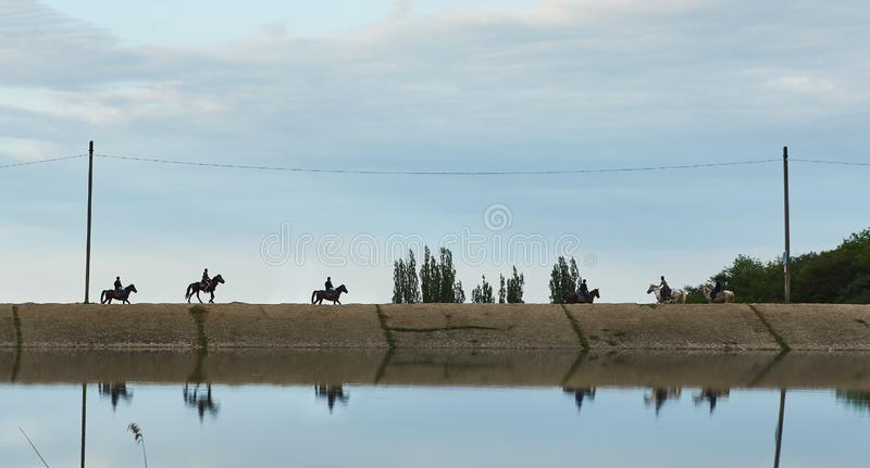 Silhouettes of riders on horseback walk along the road across the river stock photo