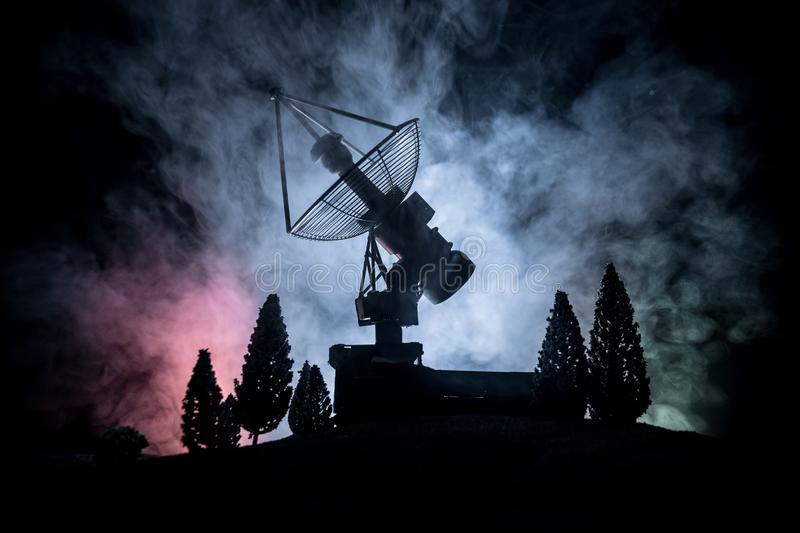 Silhouettes of satellite dishes or radio antennas against night sky. Space observatory. Or Air defence radar over dramatic night sky. Creative artwork vector illustration