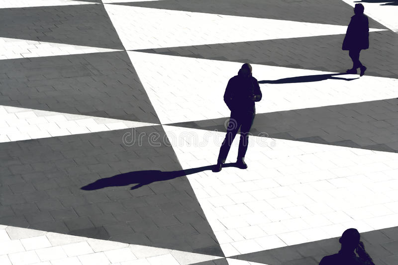 Silhouettes and shadows of people standing on an open square stock photography