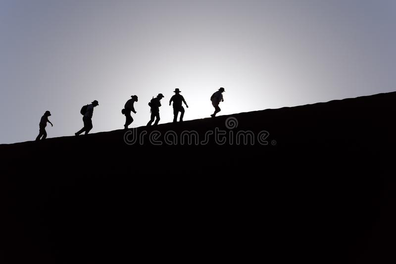 Silhouettes & shadows of six people hiking up a tall sand dune in Sossusvlei, Namib Desert, Namibia shortly after sunrise. stock image