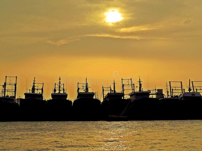 Silhouettes of ships and sunset over port of Chittagong, Bangladesh. Sunset behind clouds and silhouettes of fishing boats, port of Chittagong, Bangladesh royalty free stock photo