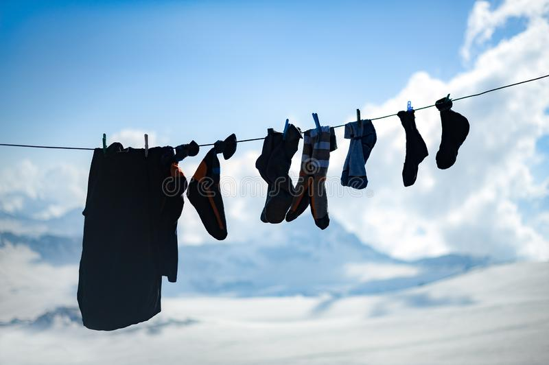 Silhouettes of socks and clothes of climbers drying on a rope high in the mountains royalty free stock photography