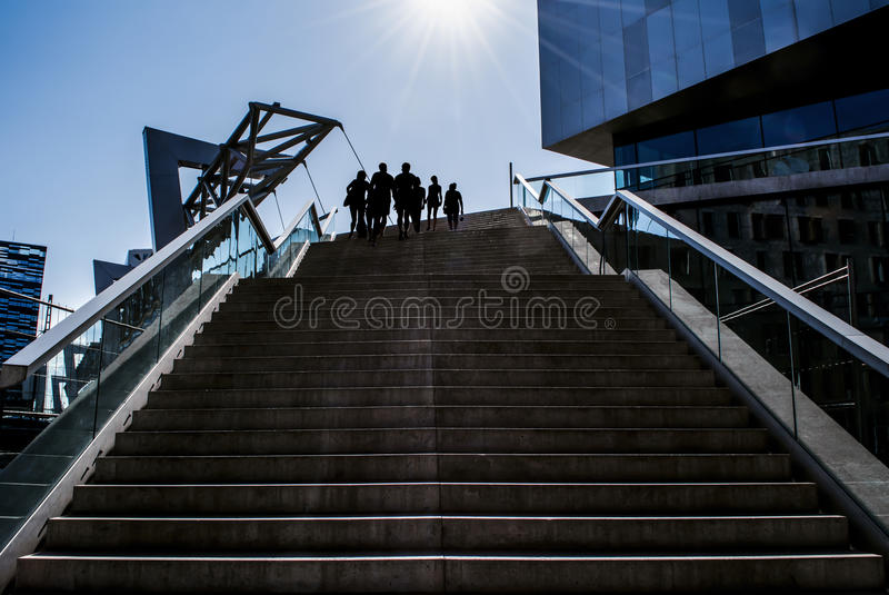 Silhouettes on stairs and modern buildings. Silhouettes of people on top of stairs and surrounded by modern buildings in Oslo, Norway. A bright, sunny day royalty free stock photography