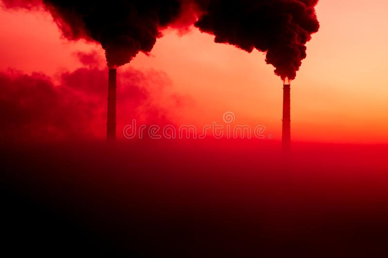 The silhouettes of the steaming pipes on the background of scarlet sunrise stock images