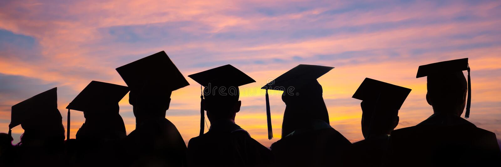 Silhouettes of students with graduate caps in a row on sunset background. Graduation ceremony web banner. Silhouettes of students with graduate caps in a row on stock images