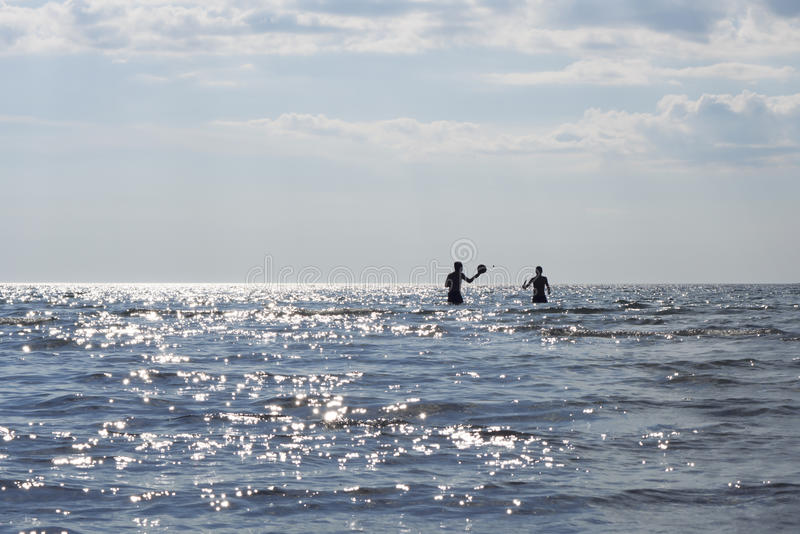 Silhouettes of sunbathers playing in the ocean. On a beautiful summer day. The water glittering stock photography