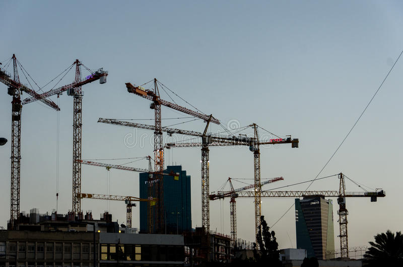 Silhouettes of tall construction cranes royalty free stock images