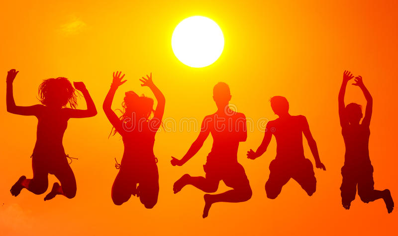 Silhouettes of teenage boys and girls jumping high in the air on royalty free stock images
